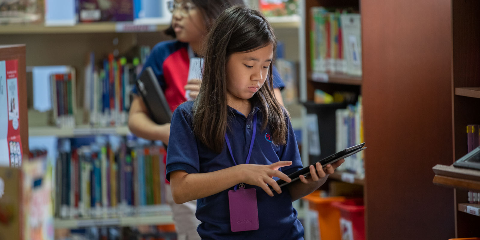 ICS Singapore elementary student using an ipad in the Library Media Center