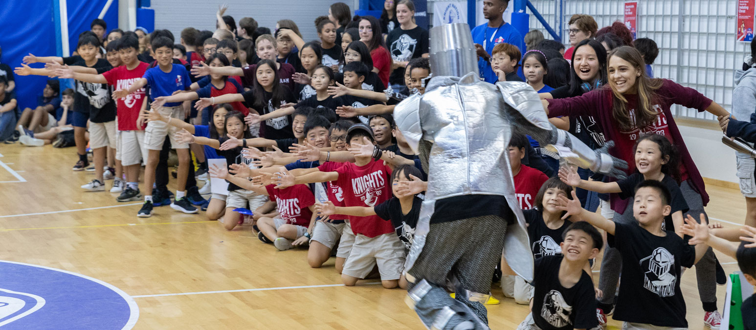 ICS Students high five mascot during pep rally