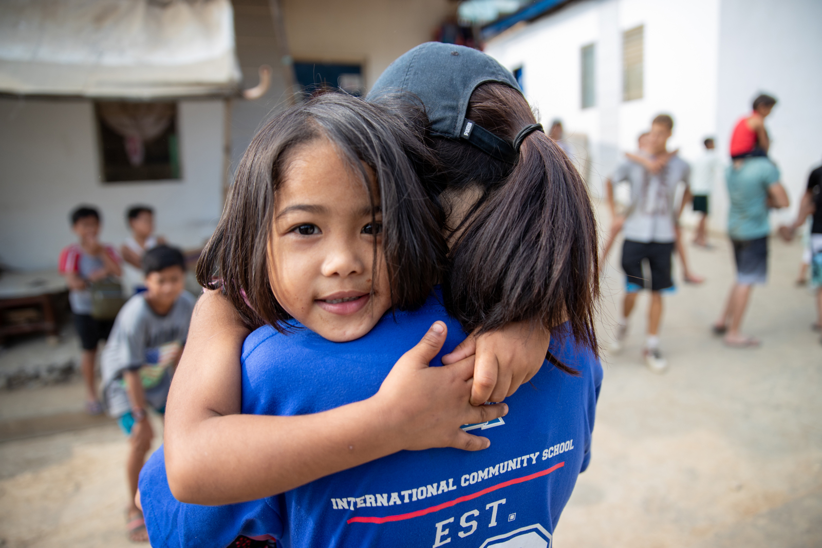 ICS Singapore high school student carrying child in Manila on service learning