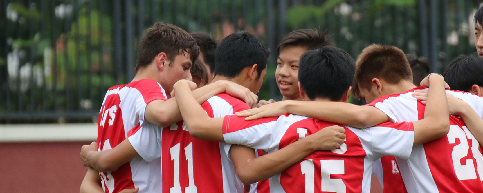 ICS Singapore varsity soccer team in a pre-game huddle