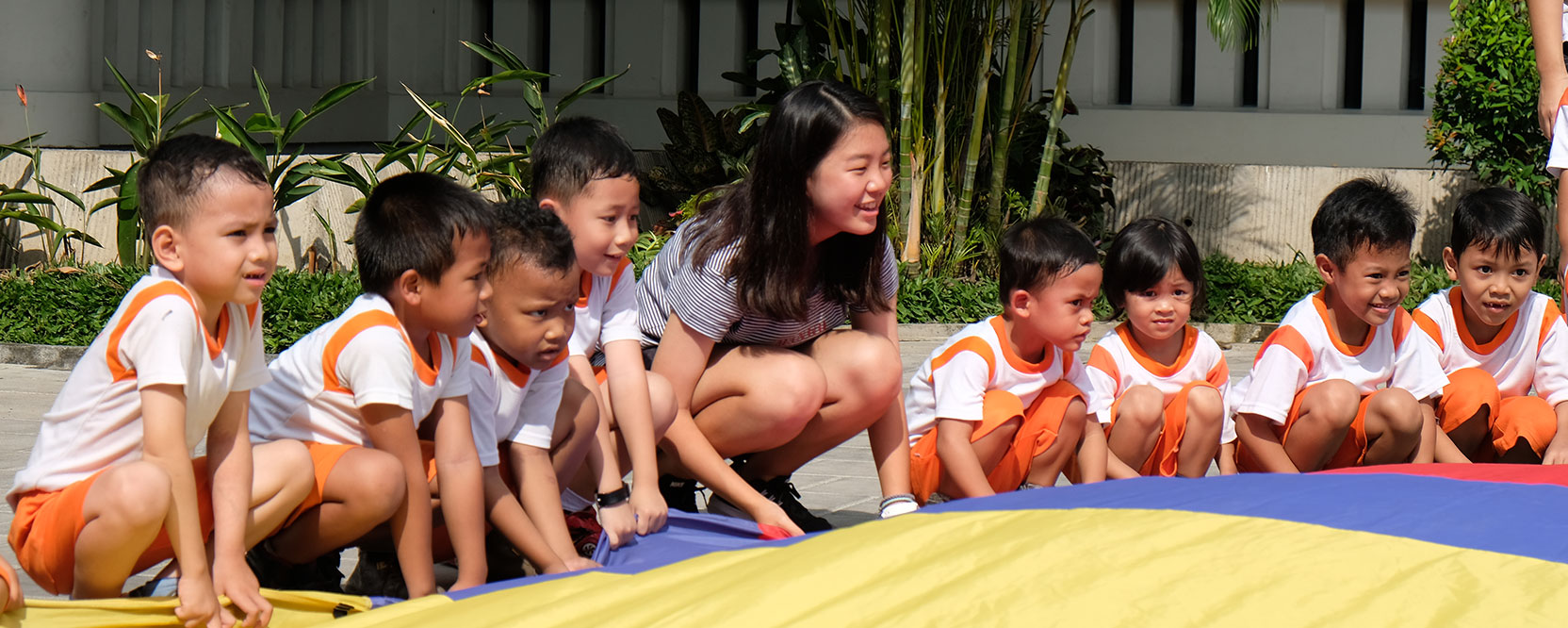 ICS Singapore high school student playing with Indonesian children on service learning trip